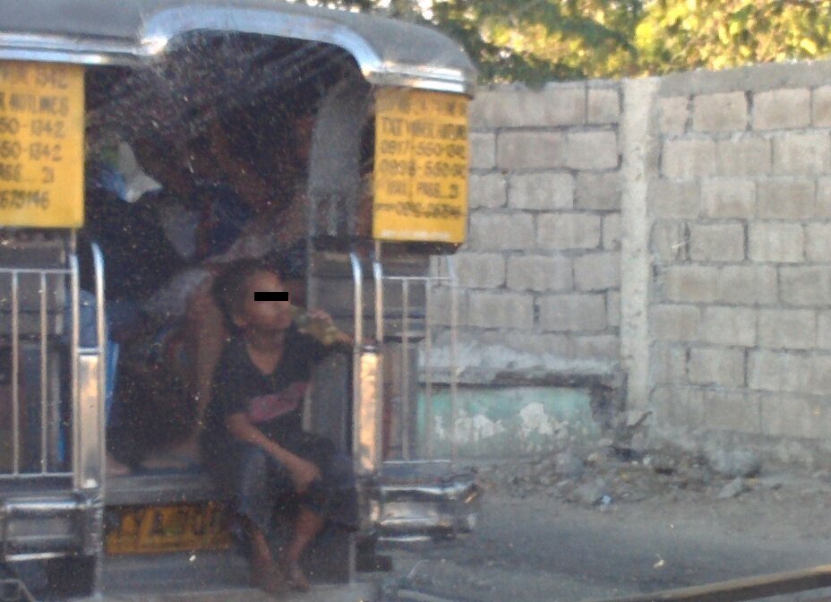 A kid hops at the back of a passenger Jeepney asking passengers to give him money while inhaling super glue